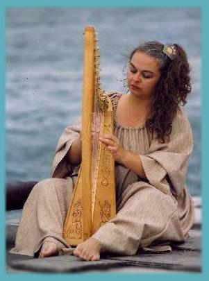 Photo of Jacquelyn playing harp on beach
